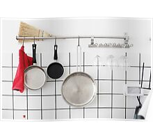 Frying pans hang on a wall of a domestic kitchen  Poster