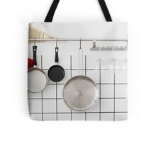 Frying pans hang on a wall of a domestic kitchen  Tote Bag