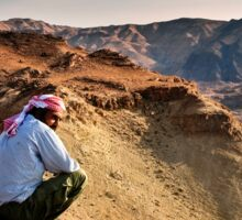 A local beduin looks out over the desert mountains Photographed in Jordan Sticker