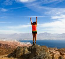 Female hiker celebrates her achievement on reaching the summit of the colourful Eilat mountains Sticker