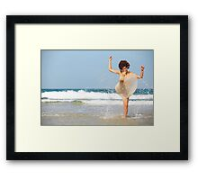 woman splashes sea water on the beach  Framed Print
