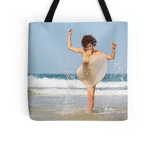 woman splashes sea water on the beach  Tote Bag