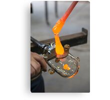 Glassblower cuts molten glass with a hand tool Canvas Print