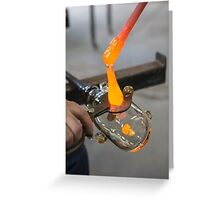 Glassblower cuts molten glass with a hand tool Greeting Card