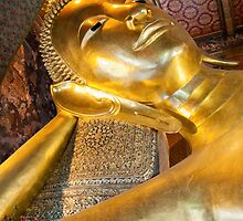 Face of Reclining Buddha gold statue in Wat Pho buddhist temple, Bangkok, Thailand by Stanciuc
