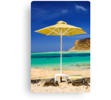 Tropical vacation - beds and umbrella on a beach Canvas Print