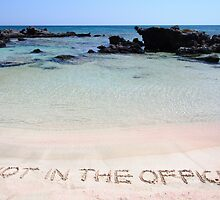 NOT IN THE OFFICE written on sand on a beautiful beach, blue waves in background by Stanciuc
