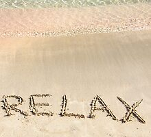 Relax word written in the sand, on a beautiful beach with clear blue waves in background by Stanciuc