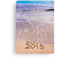 New Year 2015 is coming concept - inscription 2014 and 2015 on a beach sand, the wave is covering 2014 Canvas Print