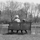 Young and old alike Great Grandfather and grandson at the pond on bench  by Jason Franklin