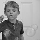 Little boy blowing bubbles black and white photo 1 by Jason Franklin