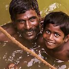 Father and son in field well, Melkavanur, India by indiafrank