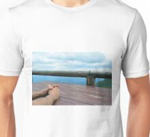 Man hands on a wooden table outside, with cloudy sky. Unisex T-Shirt