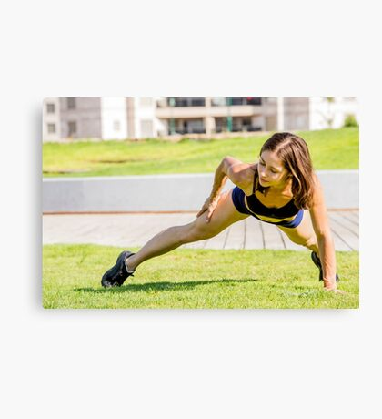 Young female bodybuilder exercises outdoors in a park Canvas Print
