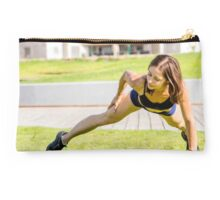 Young female bodybuilder exercises outdoors in a park Studio Pouch