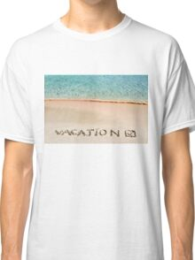 Vacation and checked mark written on sand on a beautiful beach, blue waves in background Classic T-Shirt