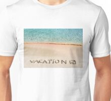 Vacation and checked mark written on sand on a beautiful beach, blue waves in background Unisex T-Shirt