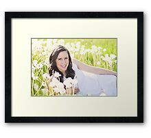 Beautiful young woman sitting in the grass Framed Print