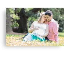 Pregnant woman with her husband in the garden Canvas Print