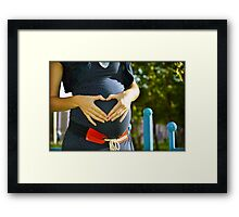 Pregnant woman making heart with her hands Framed Print
