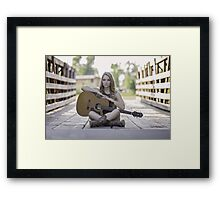 Pretty and young woman playing a guitar Framed Print