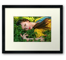Attractive woman lying in the green grass Framed Print