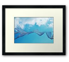 Cloth in the wind against the blue cloudy sky. Framed Print