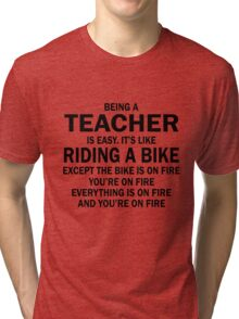 BEING A TEACHER IS EASY.IT'S LIKE RIDING A BIKE EXCEPT THE BIKE IS ON FIRE YOU'RE ON FIRE EVERYTHING IS ON FIRE AND YOU'RE ON FIRE Tri-blend T-Shirt