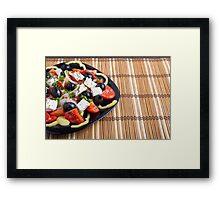 Fresh vegetarian salad in a black plate on a bamboo mat closeup Framed Print