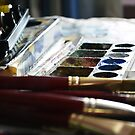 Brushes and colours behind art by nksran