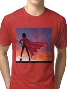 Superhero woman cartoon heroically overlooking the sunrise or sunset. Tri-blend T-Shirt
