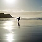surfer and people silhouette out on the beach by morrbyte