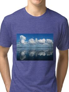 Brilliant white clouds in a rich azure-blue sky reflected in smooth sea. Tri-blend T-Shirt