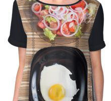 Fried egg with yolk on a black plate and a salad of tomato Chiffon Top