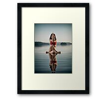 Woman doing sitting variation of yoga Eagle pose on the water art photo print Framed Print