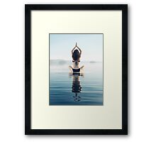 Back of a woman practicing yoga meditation on the water in sunrise mist art photo print Framed Print
