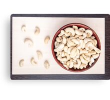 Top view on raw cashew nuts for vegetarian food in a small wooden bowl Canvas Print