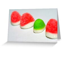 A line of red colourful sugared jelly sweets with one green one in the centre Greeting Card