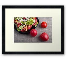 Fresh tomatoes and a part of a plate with vegetarian salad Framed Print