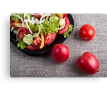 Fresh tomatoes and a part of a plate with vegetarian salad Canvas Print