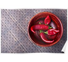 Top view of hot red chili peppers in a brown wooden bowl Poster