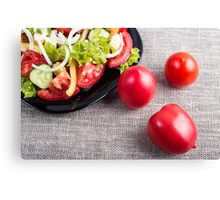 Close-Up top view on fresh tomatoes and a bowl of vegetarian salad Canvas Print