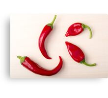 Hot red chili peppers on a light wooden board Canvas Print