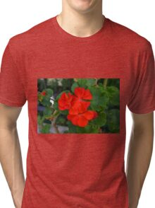 Red powerful color flower and green leaves background. Tri-blend T-Shirt