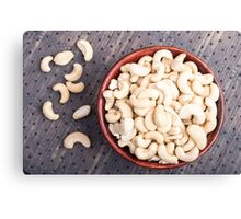 Raw cashew nuts in a brown bowl on fabric background Canvas Print