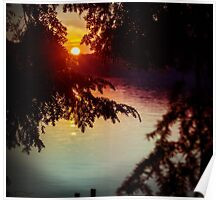 setting sun shining through the trees and reflecting off a northern lake Poster