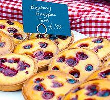 Delicious round raspberry tarts in British market by Stanciuc