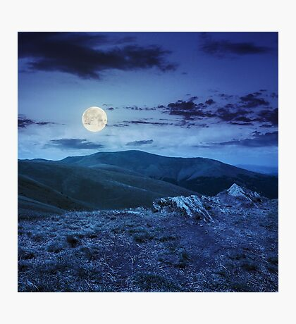light on stone mountain slope with forest at night  Photographic Print