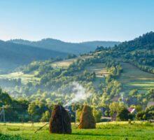 field with haystack on hillside in mountains Sticker