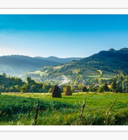 field with haystack on hillside in mountains Sticker